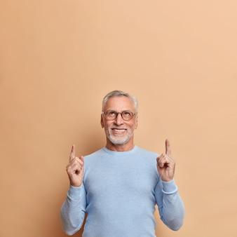L'uomo maturo positivo sicuro di sé indica sopra uno spazio vuoto dimostra la pubblicità sopra la testa vestita con un maglione blu casual isolato sopra la parete marrone