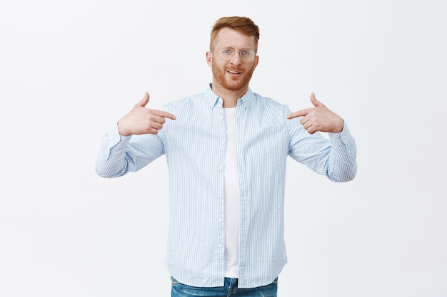 Self-assured proud redhead male entrepreneur in shirt over t-shirt pointing at himself and staring with pride, bragging about own achievements, feeling confident over gray wall