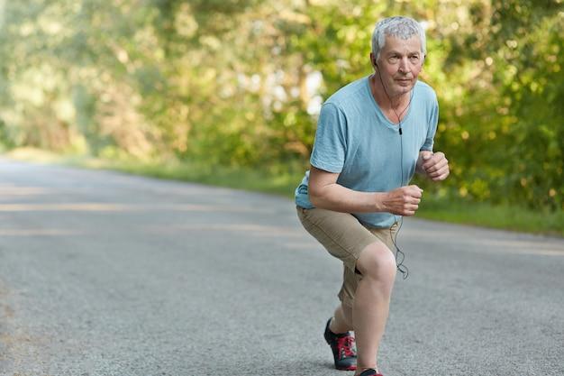 Self assured senior sportsman ready to start jogging marathon
