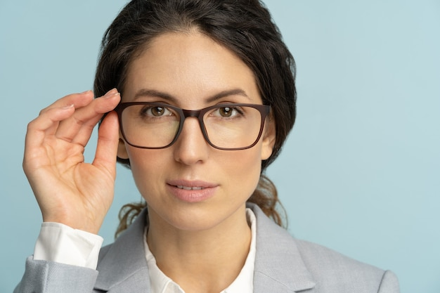 Self-assured serious business woman touches eyeglasses