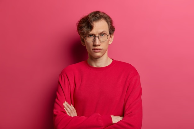 Self assured serious man keeps arms folded, looks directly  with confident expression, has wavy hair, thinks over future plans, wears spectacles and red jumper, isolated on pink wall