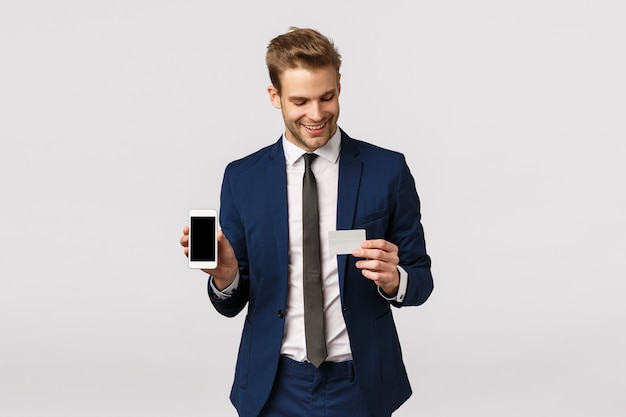 Self-assured young blond businessman in blue classic suit, holding smartphone and credit card, showing mobile display, online payment method, finance application, standing white background