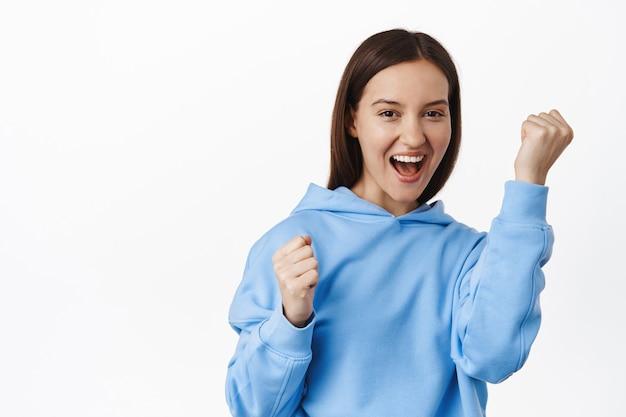 자신감 넘치는 젊은 여성은 격려를 받고 주먹을 들고 자신감 있게 웃고, 응원하고 노래하고, 승리하고 승리하며 흰 벽에 기대어 서 있습니다.