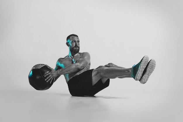 Self-building. young caucasian bodybuilder training over studio background in neon light. muscular male model with the ball. concept of sport, bodybuilding, healthy lifestyle, motion and action.