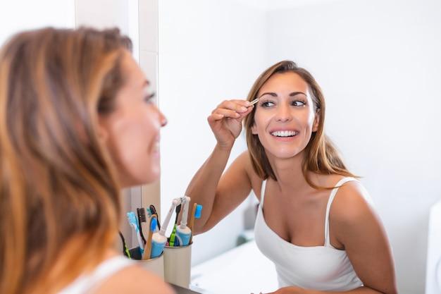 자기 관리 및 메이크업 개념. 화장실에서 거울 전에 핀셋으로 그녀의 눈썹을 따 버릴 흰 셔츠에 젊은 신중한 여자의 초상화를 허리