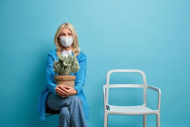 자기 관리와 집에 머물기 개념. 격리 된 여자는 선인장 냄비와 함께 편안한 의자에 진지하게 앉아있다.
