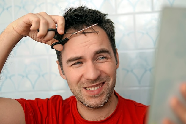 Self-care in the conditions of global quarantine and closed hairdressers and beauty salons. handsome man cutting his own hair with a scissors and looks in the mirror. trim your bangs. stay at home
