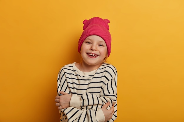 Self care and coziness concept. lovely cheerful girl embraces her body, feels comfort in new striped jumper, feels upbeat, looks positively , poses against yellow wall, loves herself
