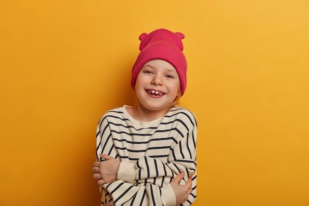 Concetto di cura di sé e intimità. bella ragazza allegra abbraccia il suo corpo, si sente a suo agio nel nuovo maglione a righe, si sente ottimista, guarda positivamente, posa contro il muro giallo, ama se stessa