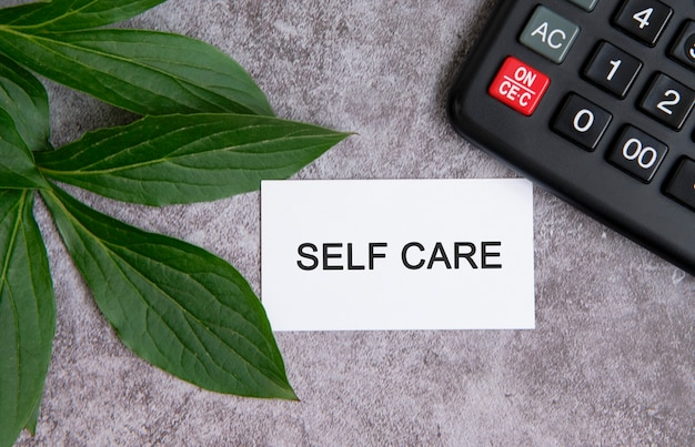 Self care - text on a grey concrete table with a calculator and green leaves