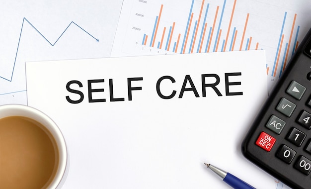 Self care - text on a white paper with a calculator and pen, and coffee to maintain immunity