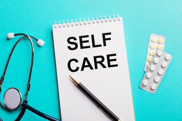 Самоуход, написанный в белом блокноте рядом со стетоскопом, ручками и таблетками на голубом фоне. медицинская концепция