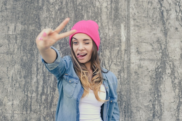 Self-confidence concept. happy smiling winking and flirting woman dressed in casual clothes and pink hat showing v-sign against stone background