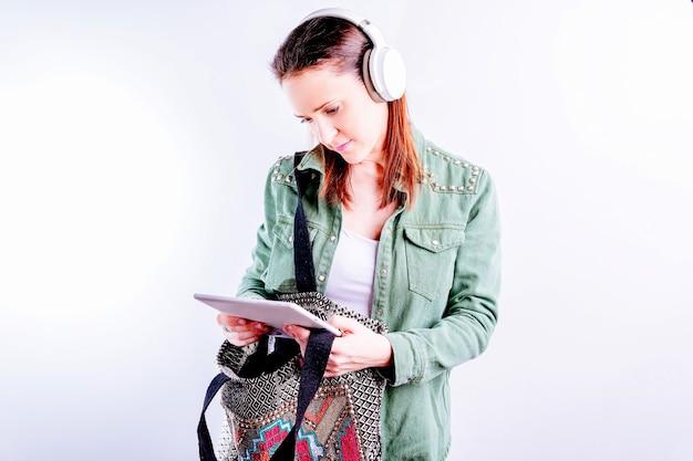 Уверенная в себе красивая молодая женщина на белом фоне в повседневной одежде и наушниках, глядя на планшет с работы