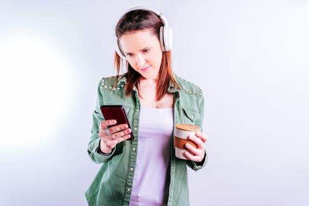 Уверенная в себе красивая молодая женщина на белом фоне в повседневной одежде и смотрит в музыкальных наушниках, ставя музыку на смартфон