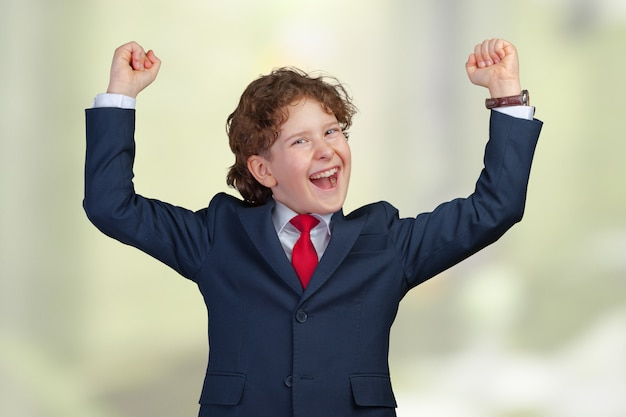 Self confident boy with raised fists celebrating a recent success