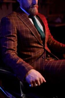 タキシードの自信に満ちた残忍な男性は屋内で熟考されています、エレガントな男性は椅子に座ってポーズをとっています