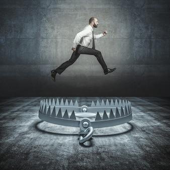 Самоуверенный бизнесмен прыгает в большую медвежью ловушку. концепция преодоления проблем и невзгод.