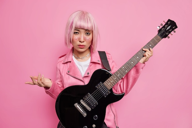 Self confident fashionable female rocker with rosy hair prepares for music festival practices acoustic guitar wears jacket poses against pink wall. talented musician play musical instrument