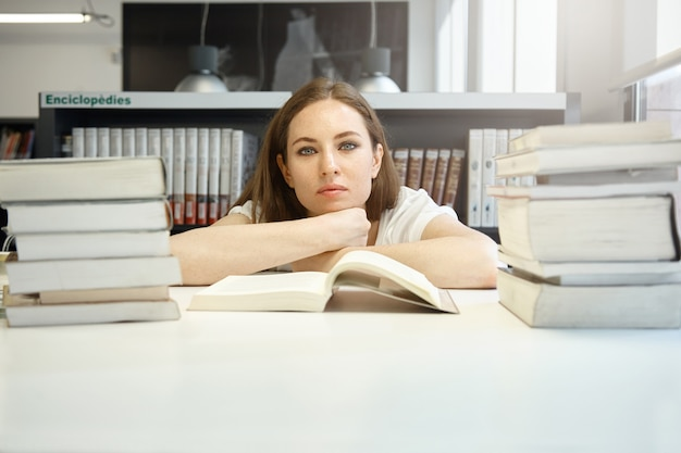 図書館で勉強する自信のある女子学生、穏やかな表情で見て、あごを手にしてテーブルに座って、外国語を学び、教科書を読む