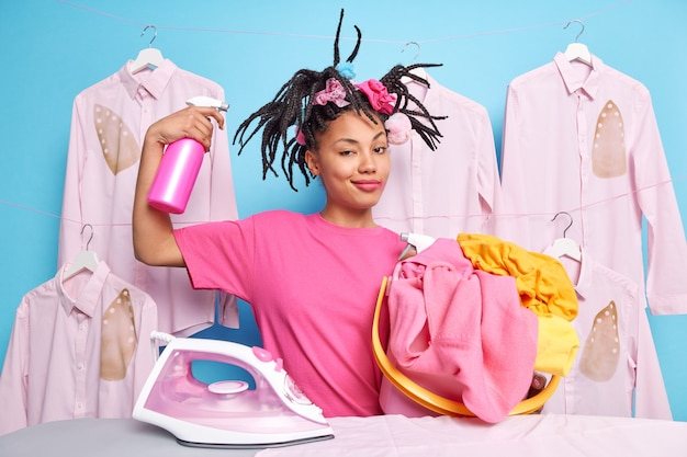 Self confident housewife with funny hairstyle raises arm with water spray carries bucket full of washed unfolded laundry uses electric iron