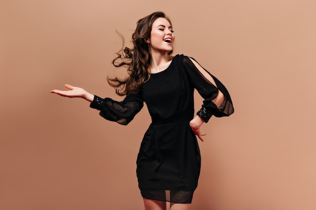 Self-confident lady in short black dress laughs and plays her hair on beige background.