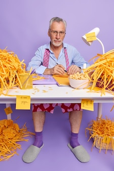 Il regista maschio sicuro di sé lavora da casa durante la pandemia di coronavirus prende appunti si siede sul desktop disordinato fa colazione in posa in ufficio domestico contro il muro viola