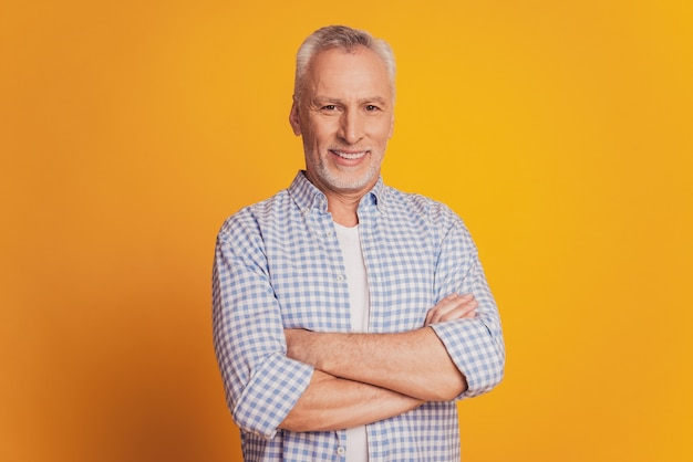 Self confident man keeps hands crossed looks at camera isolated over yellow background