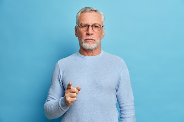 L'uomo barbuto maturo sicuro di sé indica davanti e seleziona che guardi seriamente la telecamera sceglie qualcuno nella sua squadra che indossa un maglione casual isolato sopra il muro blu