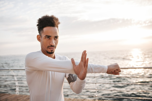 Self-confident motivated curly dark-skinned man in sport long-sleeved white t-shirt works out and looks straight near sea