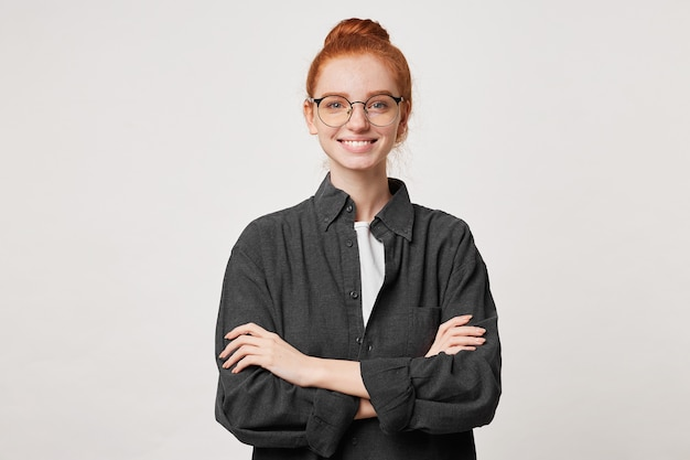 Self-confident red-haired girl with hair gathered in bun in a men's black shirt