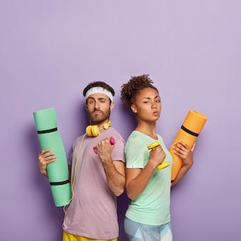 自信を持って真面目で多様な女性と男性がお互いに立ち向かい、ダンベルで腕を上げ、カレマットを握り、体力を発揮し、体調が良く、紫色の壁に隔離されています
