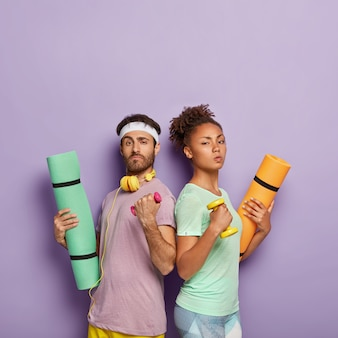 Self confident serious diverse woman and man stand back to each other, raise arms with dumbbells, hold karemats, show their strength, being in good physical shape, isolated on purple  wall