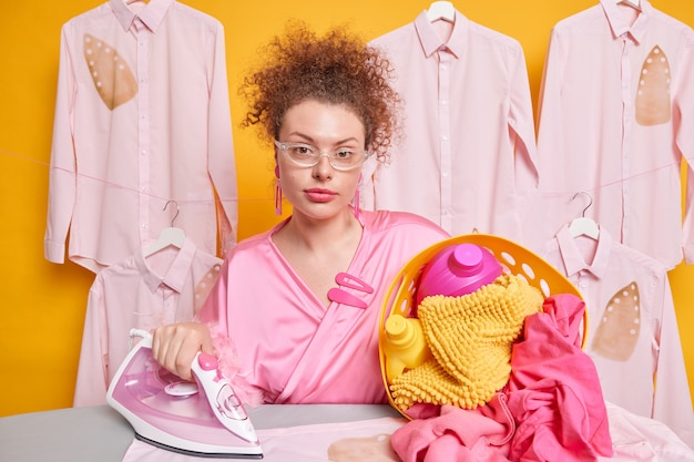 Self confident serious housemaid poses with basket full of laundry irons washed crumpled clothes wears transparent glasses dressing gown does domestic works. home duties and responsibilities