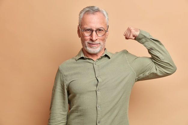 Self confident serious man raises arm shows muscles being confident in his strength wears formal shirt poses against brown wall