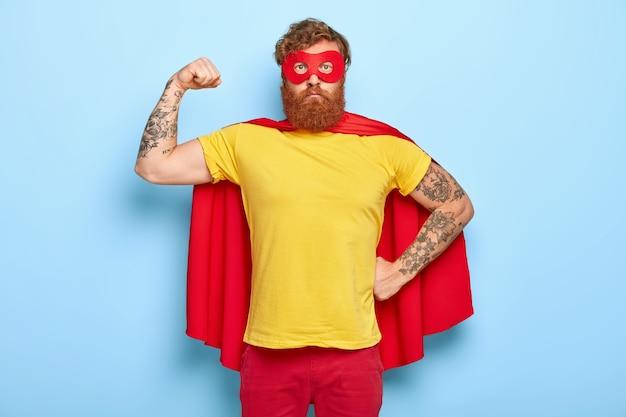 Уверенный в себе супергерой показывает бицепс, борется со злом и помогает людям