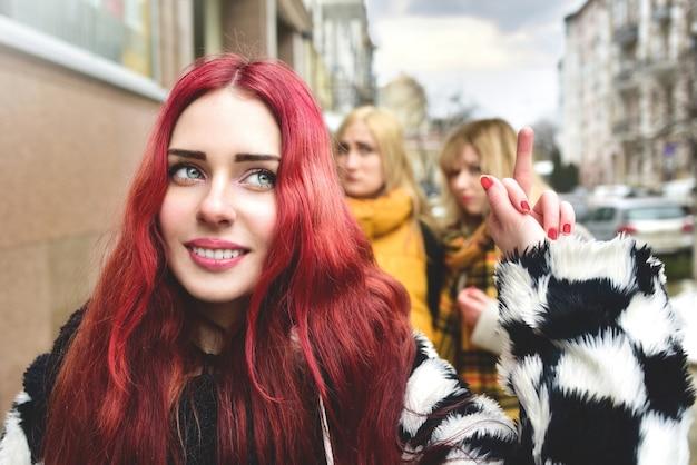 Самоуверенная девочка-подросток игнорирует ревнивых людей, которые распространяют сплетни за ее спиной. прекращать травлю. социальные проблемы. девушка показывает своим недоброжелателям средний палец.