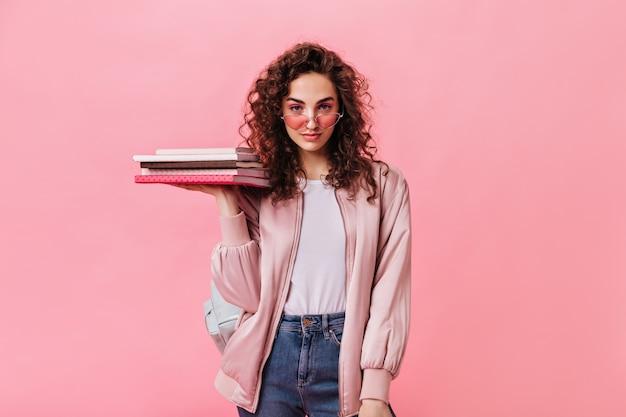 Самоуверенная женщина в модной повседневной одежде держит книги на розовом фоне