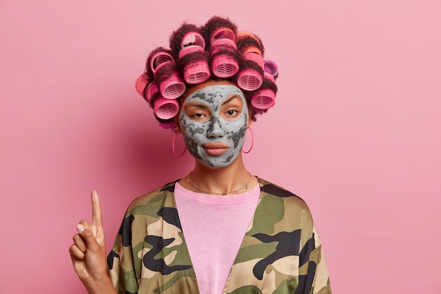 Self confident woman points above on copy space applies hair rollers and clay facial mask demonstrates beauty product dressed in domestic clothes isolated over pink wall. cosmetology concept