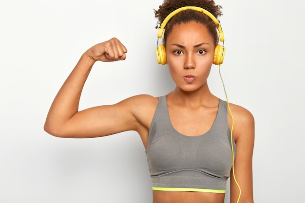 Self confident woman with serious expression, raises arm, shows biceps, listens music via modern headphones, has cardio session.