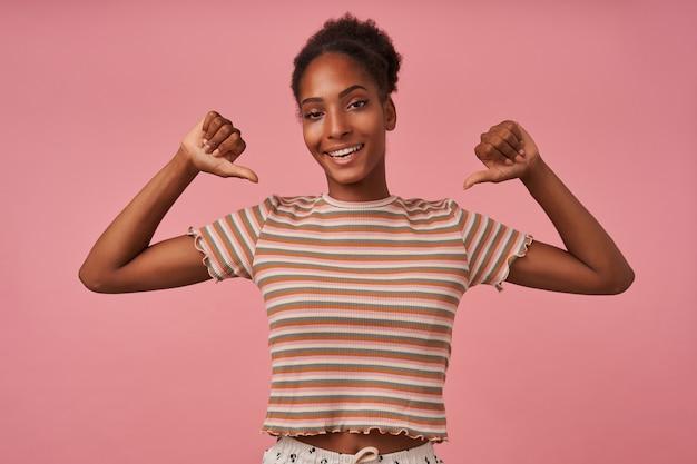자신감이 강한 젊은 예쁜 갈색 머리 곱슬 머리 아가씨는 행복하게 자신에게 엄지 손가락을 대고 캐주얼웨어에 분홍색 벽 위에 서있는 동안 넓게 웃고 있습니다.