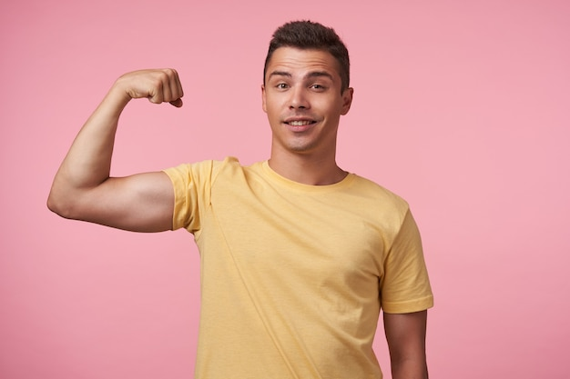 Self-confident young pretty short haired brunette guy keeping hand raised while showing his power and looking glaldy at camera, isolated over pink background