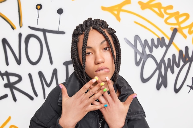 Self confindent cool teenager looks seriously at front raises hands bites lips has dreadlocks hairstyle wears fashionable clothes poses against graffiti wall