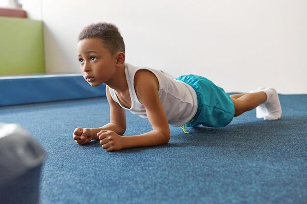 Самостоятельный афро-американский мальчик, одетый в спортивную одежду, тренируется в тренажерном зале