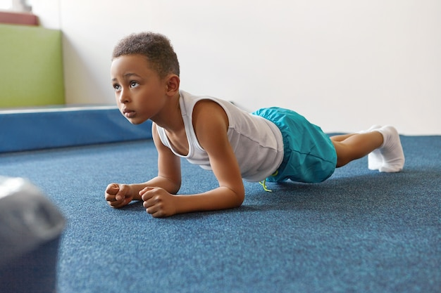 Self determined african american boy dressed in sports clothes planking at gym