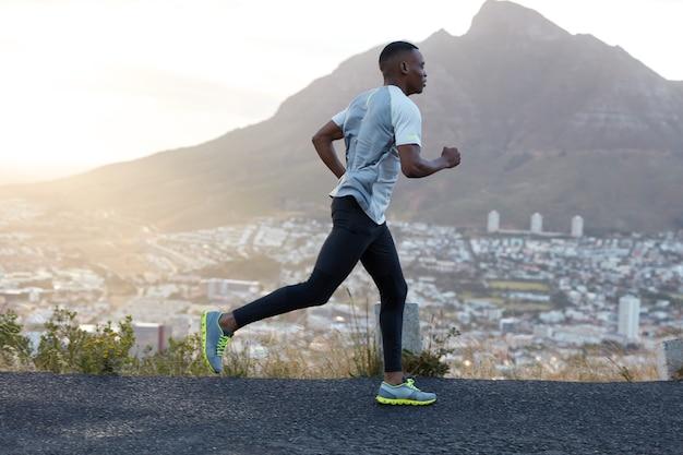 Il corridore sportivo maschio dalla pelle scura autodeterminato indossa abiti sportivi, corre su lunghe distanze su strade di montagna, gode dell'aria fresca, si sente energico e motivato. persone, stile di vita e concetto di sport