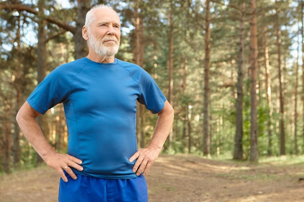 Self determined elderly man on retirement training outdoors in pine wood, holding hands on his waist, doing exercises to warm up body before run. bearded retired male catching breath after workout