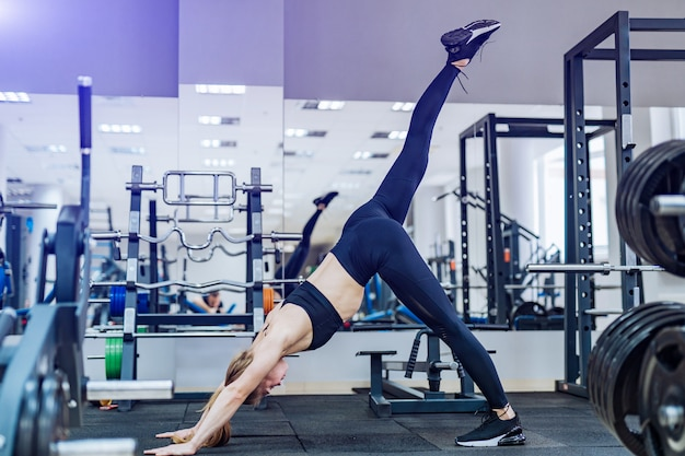 Self determined fitness woman stands on hands stretching her leg in the gym.