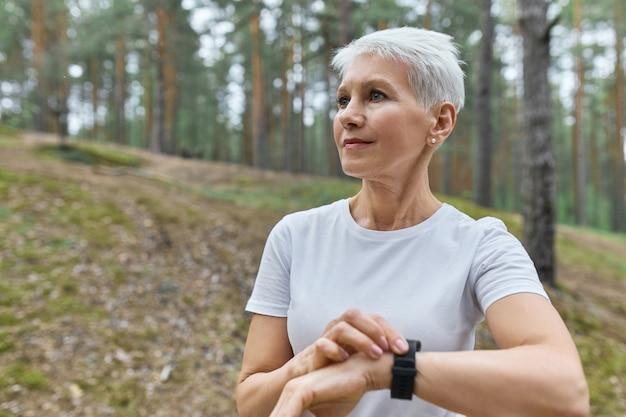 Sportiva di mezza età autodeterminata in maglietta bianca che regola orologio intelligente, controlla le statistiche di fitness, monitorando le sue prestazioni di corsa durante l'allenamento cardio nel parco