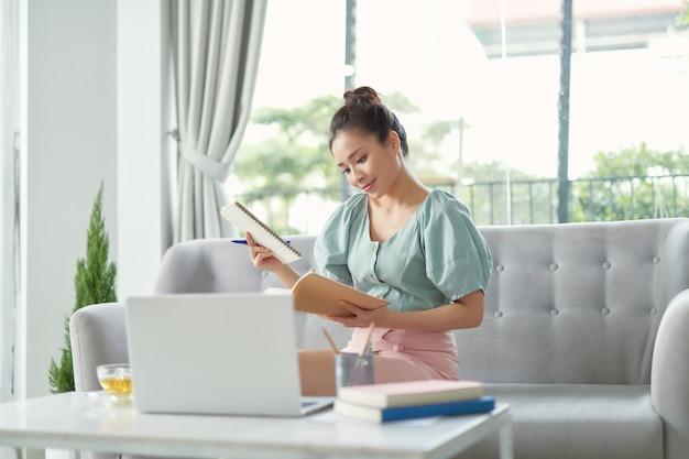 家庭での自己教育。ノートに書く集中成熟した女性